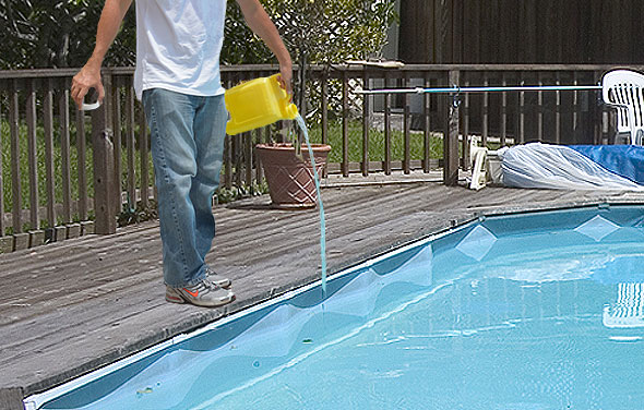 Pour chemicals into your pool